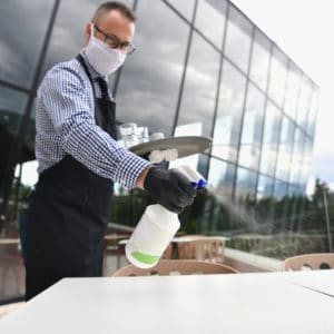 male waiter spraying disinfectant on dining table outside