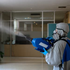 safety worker spraying disinfectant using a fogger machine